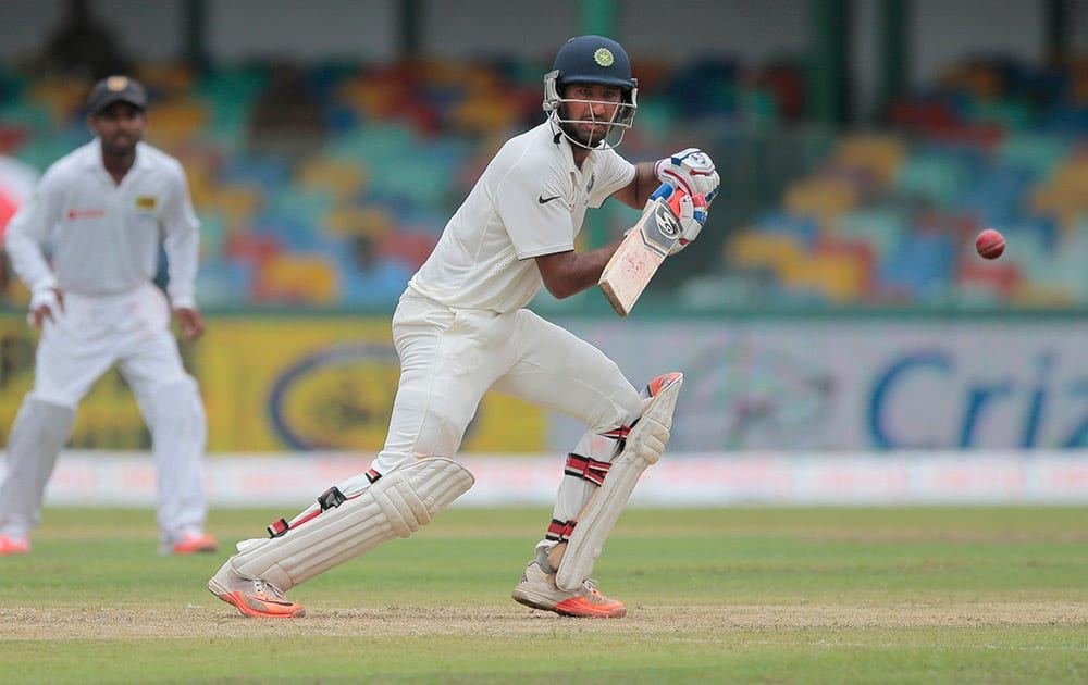 Cheteshwar Pujara plays a shot against Sri Lanka on the day one of their third test cricket match in Colombo, Sri Lanka.