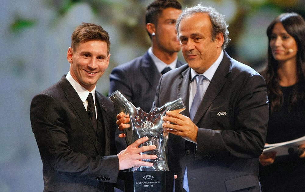 UEFA Prez Michel Platini (R) gives the trophy for best player of the year to Barcelonas Lionel Messi of Argentina, during the UEFA Champions League draw at the Grimaldi Forum.