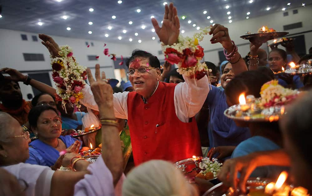 "Widows and scavenger women, earlier considered ""untouchables,"" surround Bindeshwar Pathak, founder of non-governmental organization Sulabh International, as they tie"