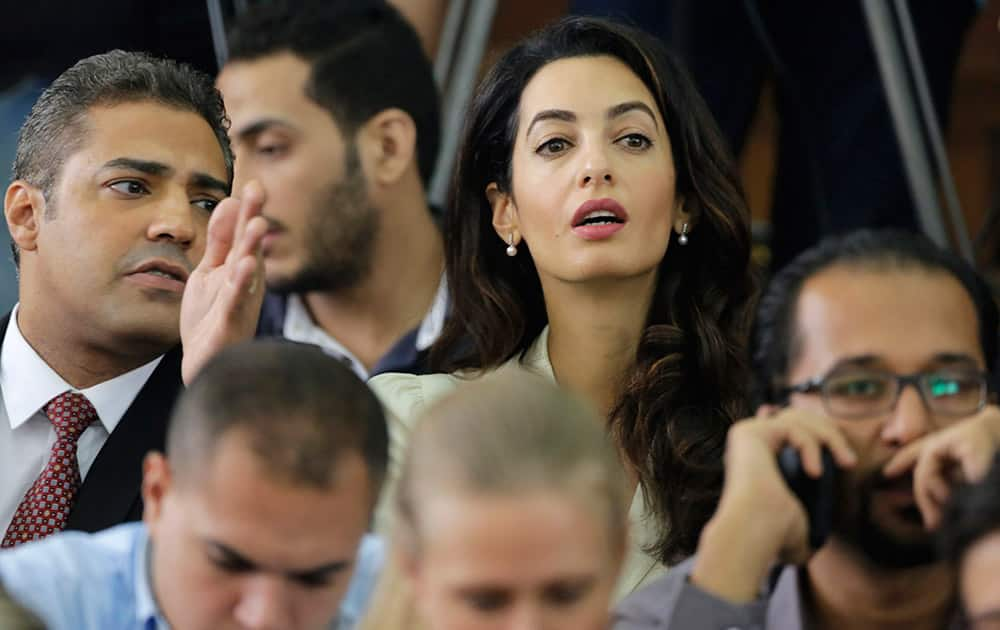 Canadian Al-Jazeera English journalist Mohammed Fahmy, left, talks to lawyer representing him Amal Clooney before his verdict in a courtroom in Tora prison in Cairo, Egypt.