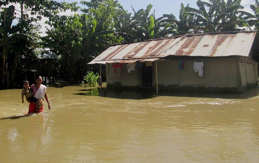 A woman walks through flood water at Ghilamara village in Lakhimpur district of Assam.