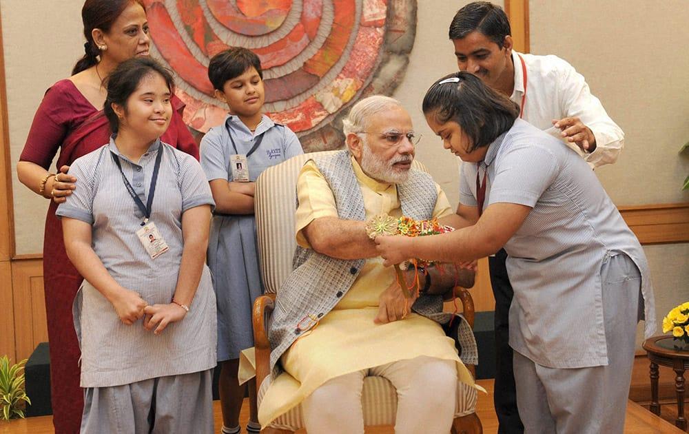 Children tying 'Rakhi' to Prime Minister, Narendra Modis wrist on the occasion of 'Raksha Bandhan', in New Delhi.