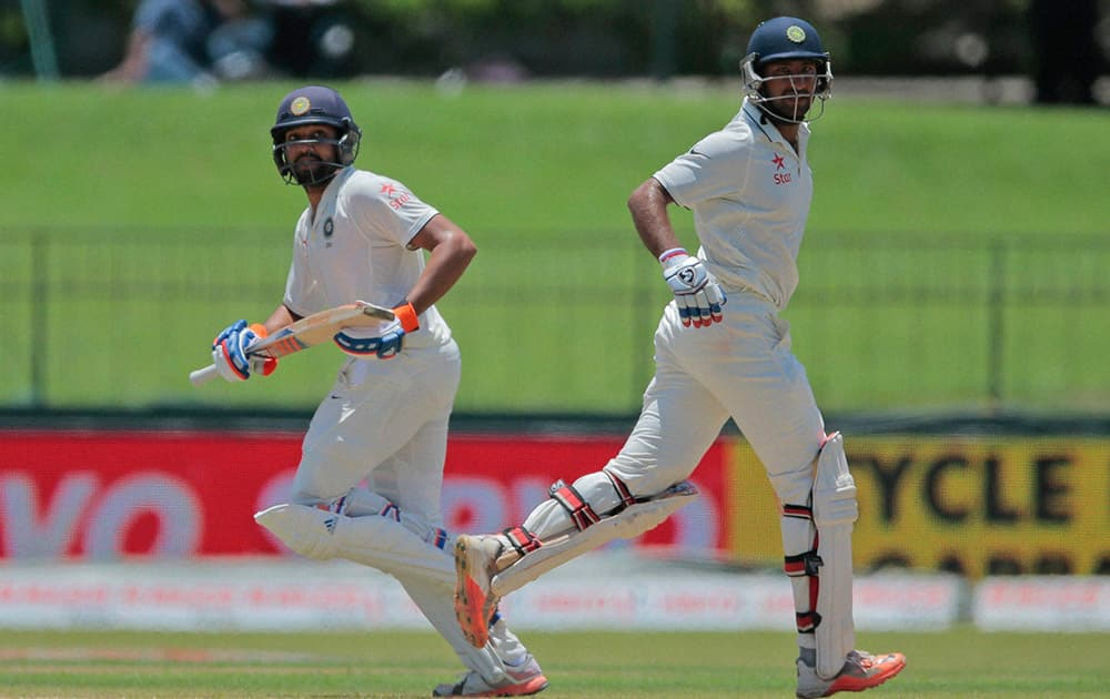Cheteshwar Pujara, right, and Rohit Sharma run between wickets on the second day of their third test cricket match against Sri Lanka in Colombo, Sri Lanka.