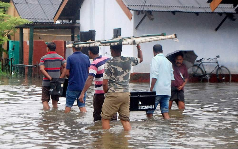 Flood affected people shift with their households in Dibrugarh.
