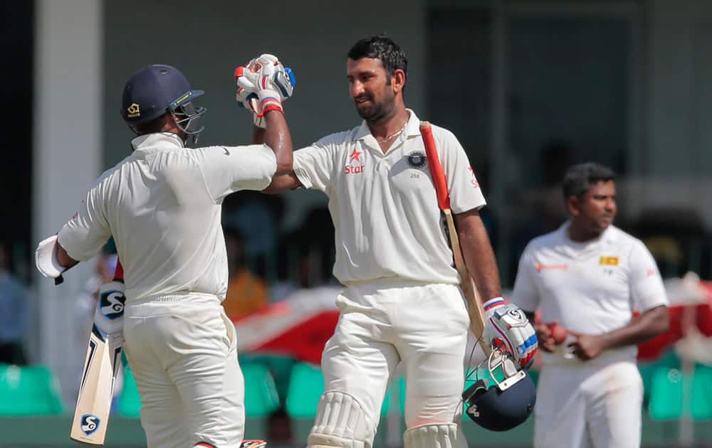 Cheteshwar Pujara, century celebrates scoring a hundred runs with teammate Amit Mishra, back to camera on the second day of their third test cricket match against Sri Lanka in Colombo.