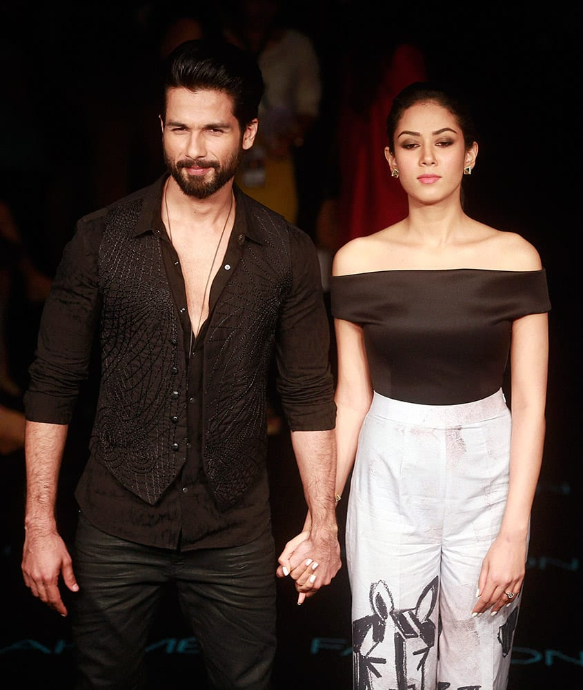 Bollywood actor Shahid Kapoor with wife Mira Rajput poses for photographs during the Lakme Fashion Week in Mumbai.