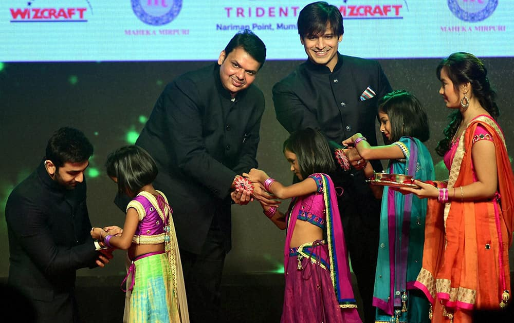Girls tie Rakhi to actor Ranbeer Kapoor, Maharashta Chief Minister, Devendra Fadnavis and actor Vivek Oberoi during a event to spread awareness against human trafficking in Mumbai.