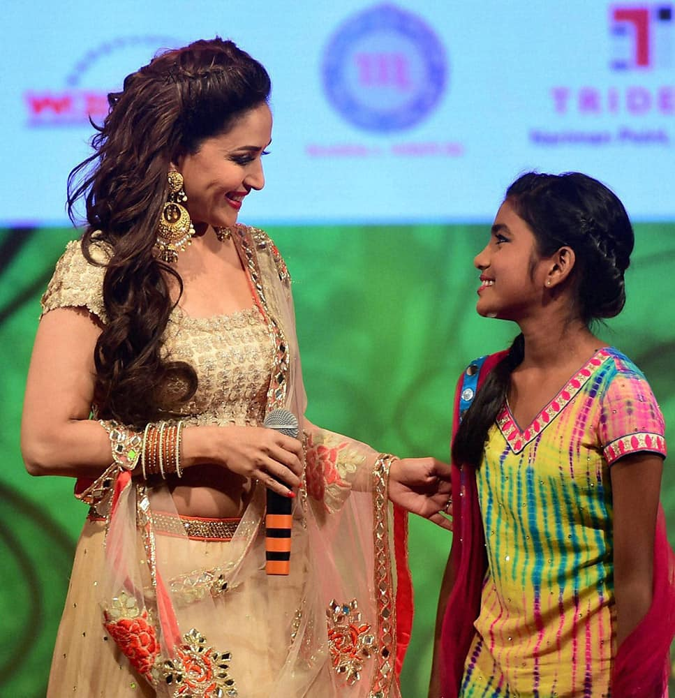 Actress Madhuri Dixit along with a beneficiary of the cause during a event to spread awareness against human trafficking in Mumbai.