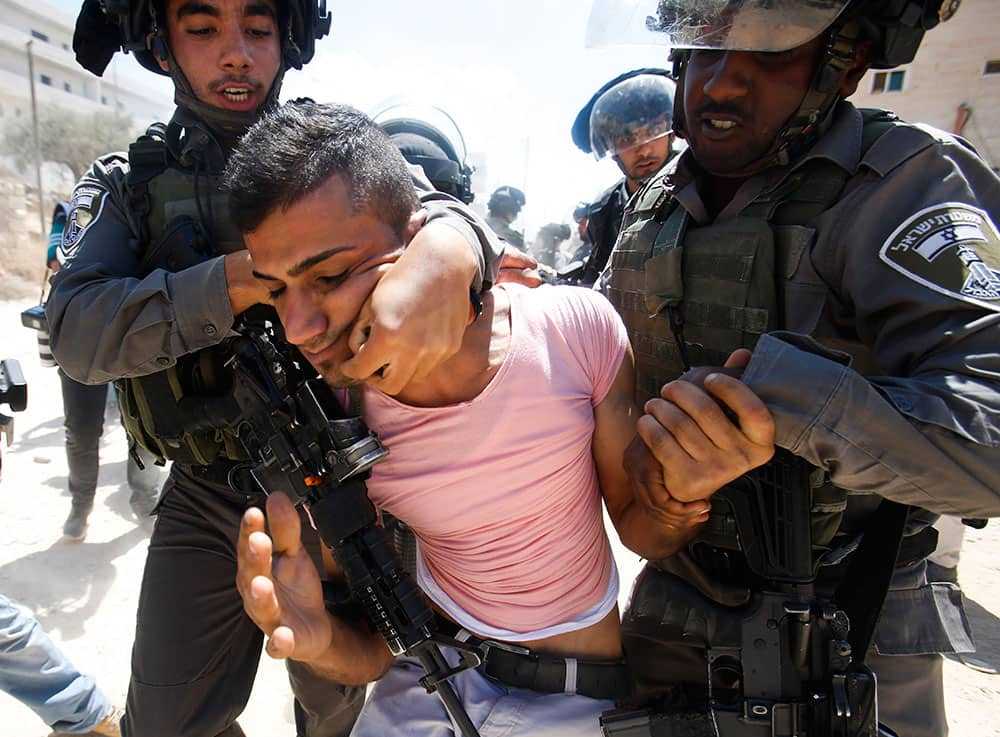 Israeli border police detain a Palestinian during a protest against the Israeli separation barrier, in Beit Jala, West Bank.