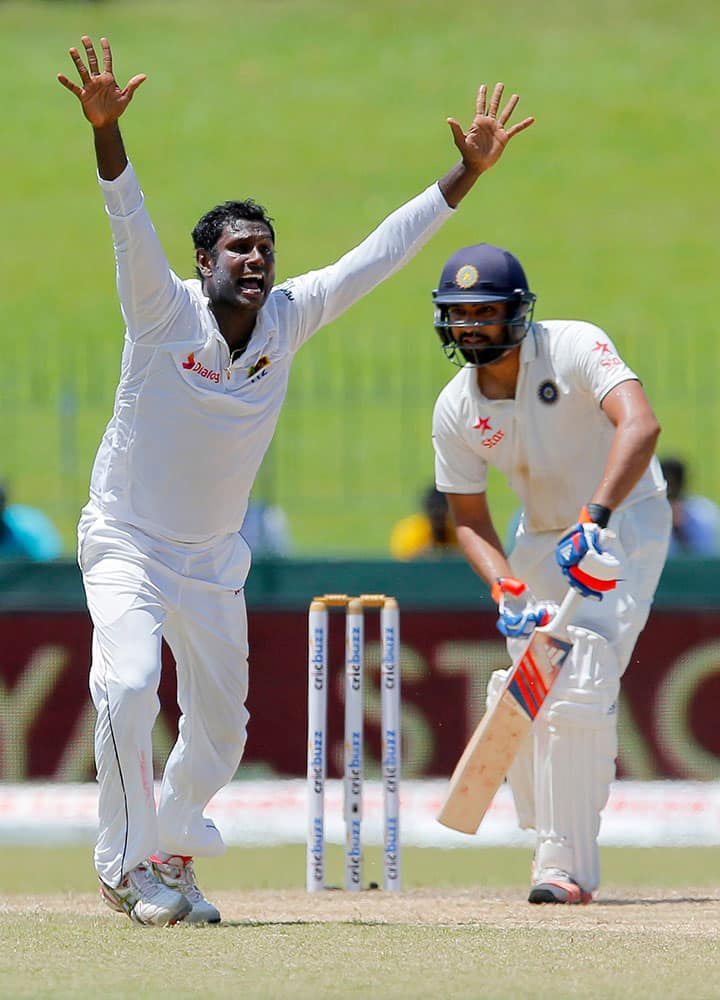 Sri Lanka's Angelo Mathews, left, unsuccessfully appeals to dismiss India's Rohit Sharma on the day four of the third cricket test match in Colombo, Sri Lanka.
