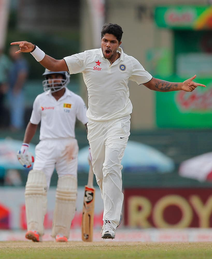 Umesh Yadav celebrates taking the wicket of Sri Lanka's Dimuth Karunarathne, unseen, on day four of the third test cricket match between them in Colombo, Sri Lanka.