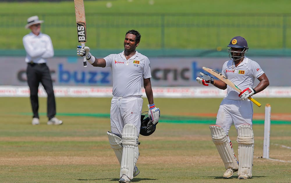 Sri Lanka's Angelo Mathews celebrates scoring a hundred as non striker Kusal Janith Perera watches on the final day of their third test cricket match in Colombo, Sri Lanka.