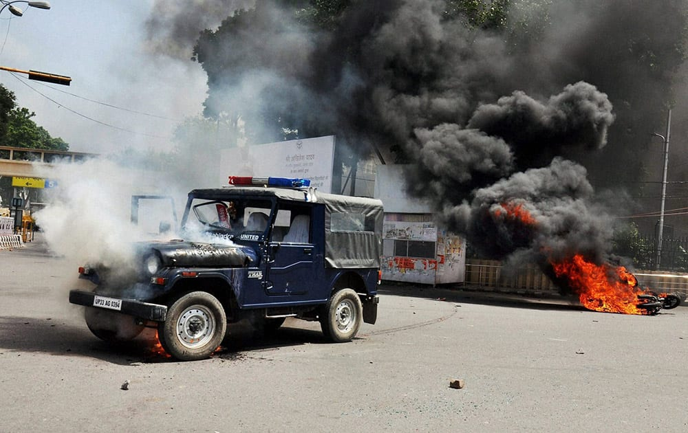 B P Ed Sangharsh Morcha members set afire vehicles during their protest for jobs in front of Vidhan Sabha in Lucknow.