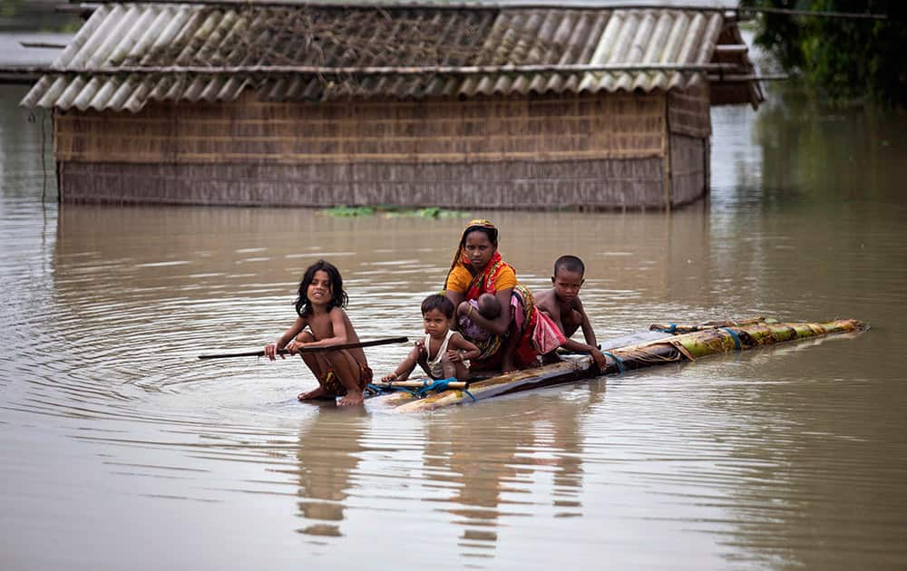 A family uses a makeshift banana raft to cross floodwaters as they try to reach safer areas at Kholabuya village, 65 kilometers (40 miles) from Guwahati.