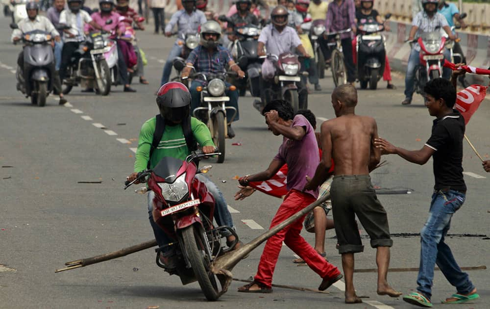 Activists of a trade union group try to stop a motorcyclist to keep vehicles off the road during a daylong nationwide strike in Bhubaneswar.