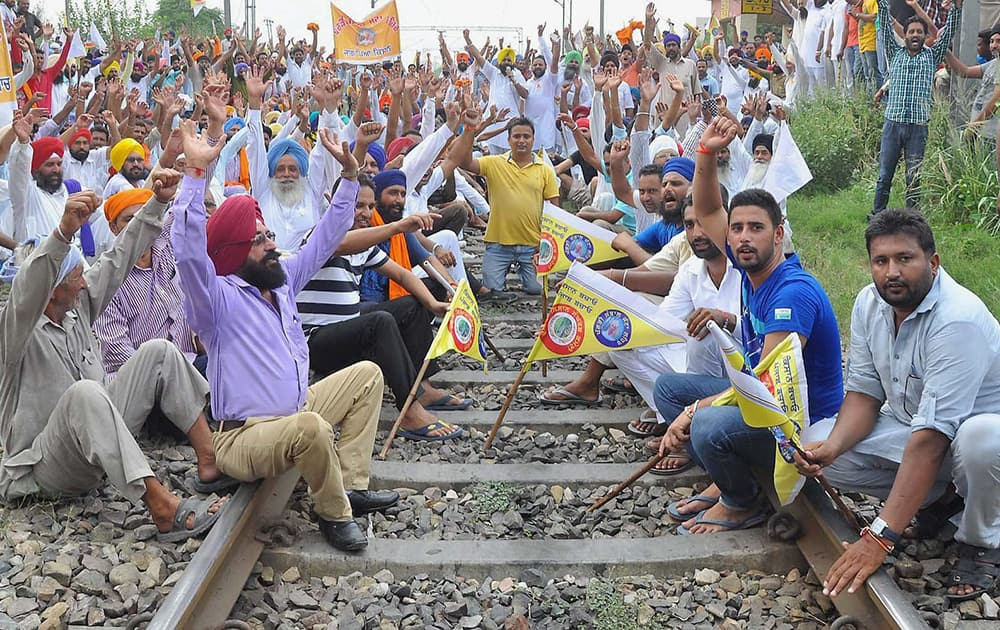 Sugarcane farmers block a rail track during a protest against the Punjab Government for not lifting their crop, in Jalandhar.