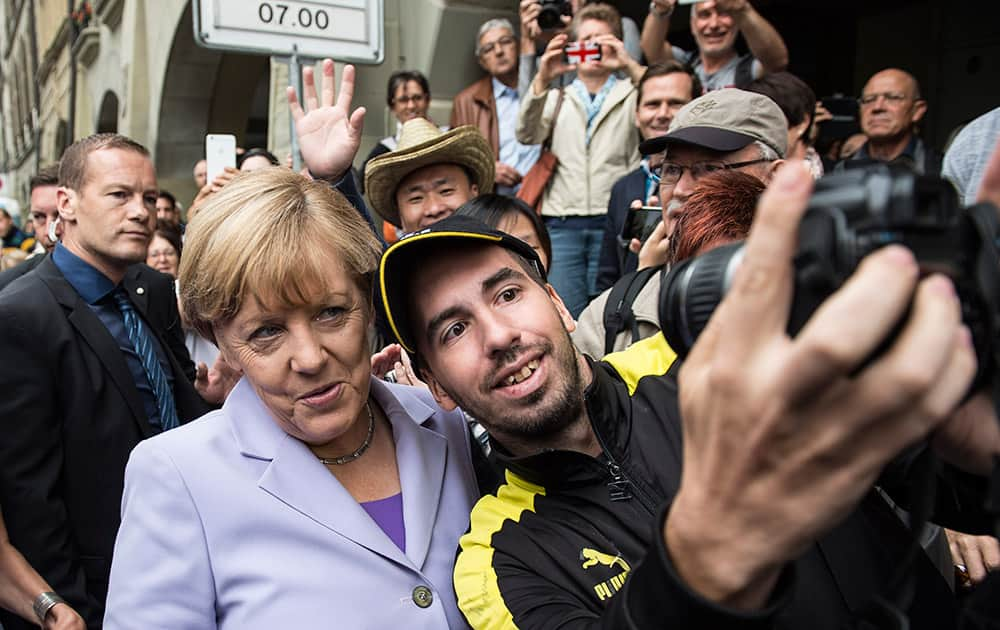 German Chancellor Angela Merkel poses for a selfie with an unknown man, in Bern Switzerland. Chancellor Merkel is on an one day official visit to Switzerland to discuss bilateral issues and the relationship between Switzerland and the EU.