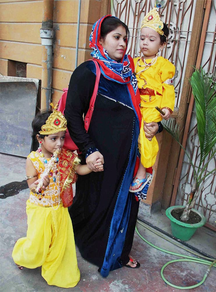 A Muslim woman with her children dressed up as Lord Krishna during a celebration program on the eve of Krishna Janmashtami festival in Allahabad.