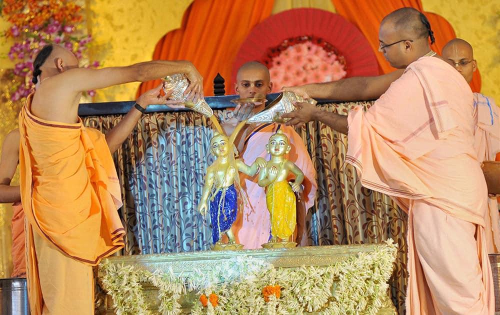 A priest performs abhishek of Lord Krishna at Krishna Balaram temple in Akshaya Patra on the occasion of Janmashtami in Jaipur.