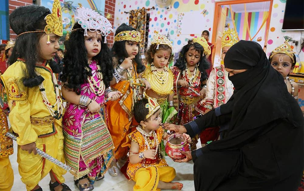 A muslim woman feeding makhan to her children dressed as Lord Krishna at a school during Krishna Janmashtami celebrations at Beawar in Rajasthan.