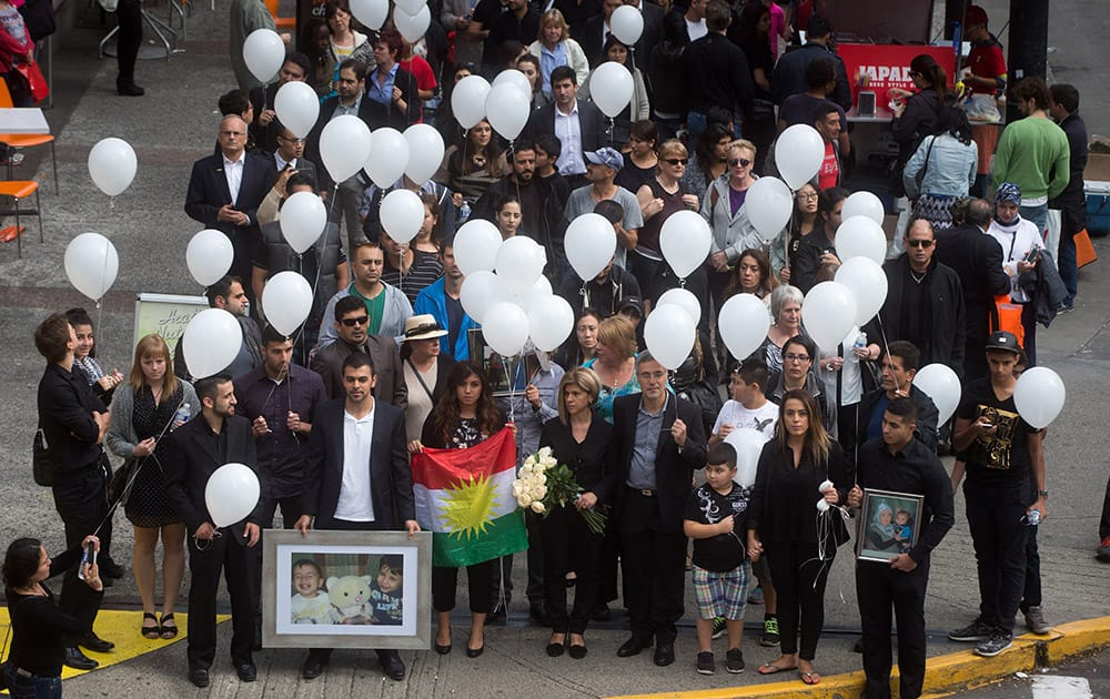 Tima Kurdi, foreground center, aunt of late brothers Alan and Ghalib Kurdi, her husband Rocco Logozzo, center right, son Alan Kerim, bottom left, holding photo, and family friend, Nissy Koye, holding flag, walk to the waterfront to release balloons in memory of the boys after a memorial service in Vancouver, British Columbia, Canada.