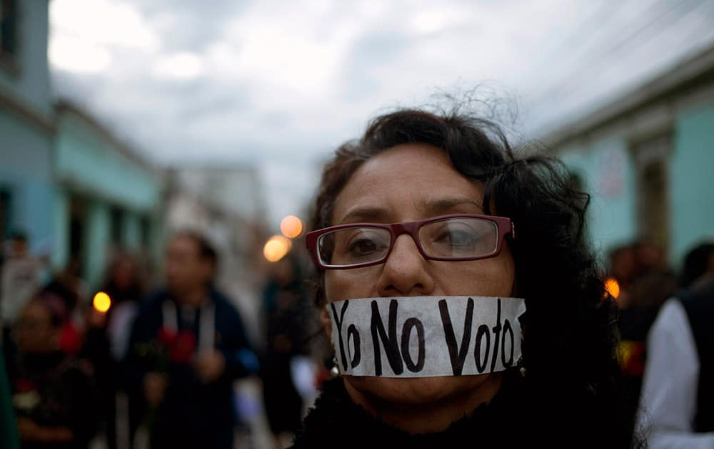 A demonstrator covers her mouth with tape carrying the message Spanish: