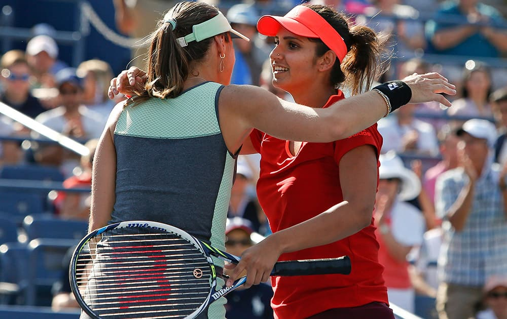 Martina Hingis of Switzerland and partner Sania Mirza, of India, celebrate after winning their doubles match during the fourth round of the U.S. Open tennis tournament.