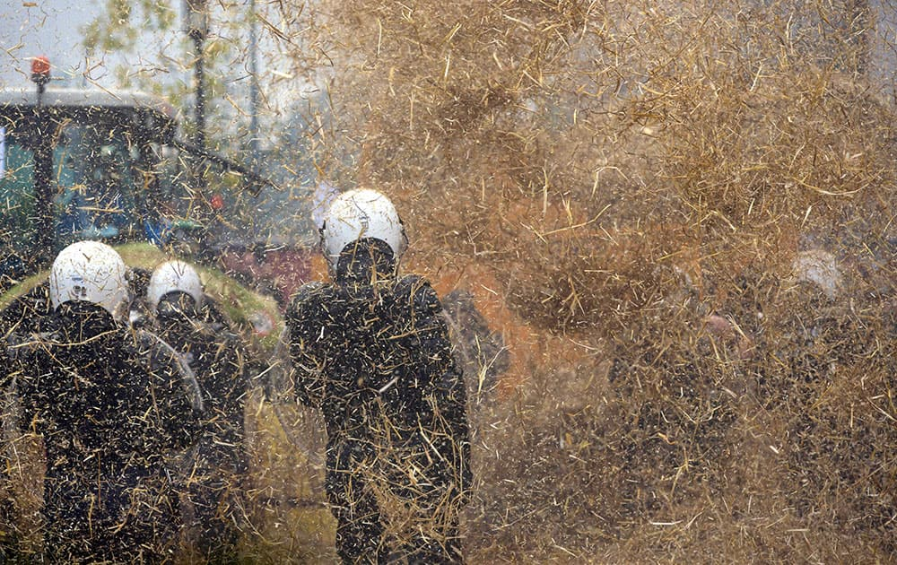 Police are sprayed with a hay machine during a farmers demonstration in Brussels.