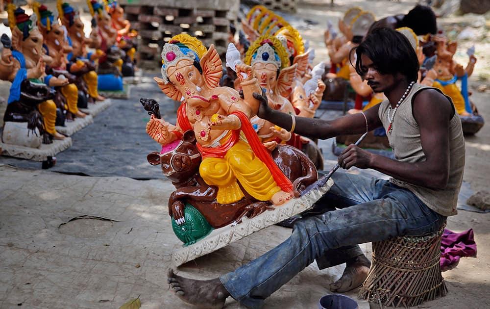 Artist paints idols of Hindu god Ganesha in Allahabad.