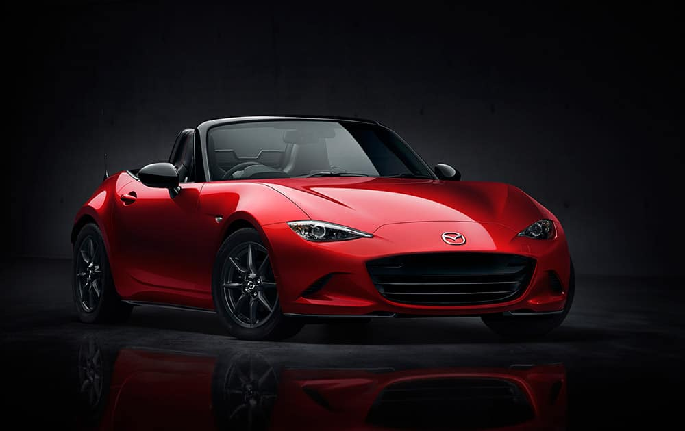 This photo provided by Mazda North America Operations shows the exterior front and side view of the new 2016 Mazda MX-5 Miata. Twenty-six years after the debut of the first Miata, Mazda is introducing the fourth generation of the popular soft-top convertible.