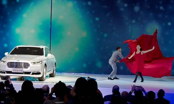Dancers perform near the Ford Taurus during the opening of the Shanghai Auto Show in Shanghai.