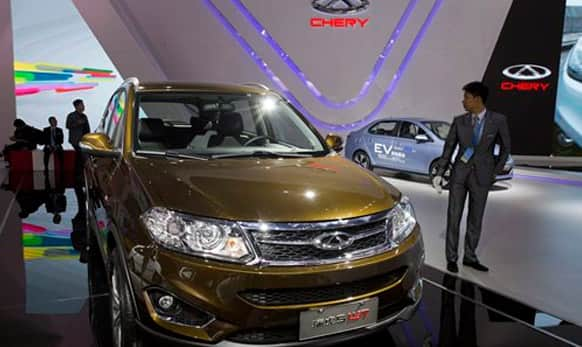 Staff wait for visitors at the booth for Chinese automaker Chery at the Shanghai Auto Show in Shanghai.