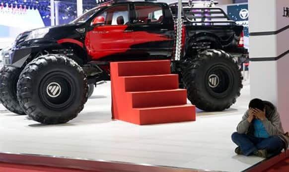 A man rests near an oversized truck displayed at the Shanghai Auto Show in Shanghai.