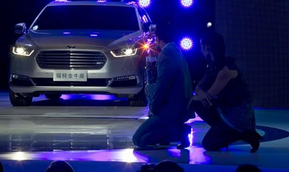 Performers unveil the Ford Taurus during the Shanghai Auto Show in Shanghai.