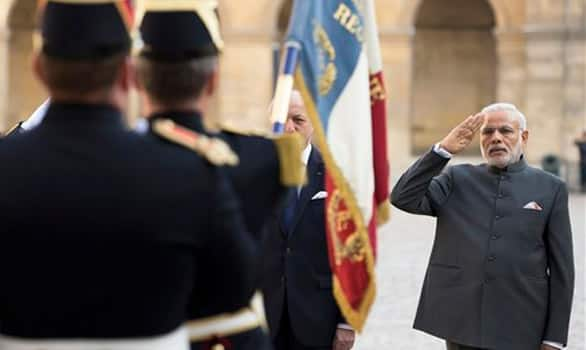 French foreign minister Laurent Fabius, partly hidden at left, and Prime Minister Narendra Modi salute the French flag during a welcoming ceremony in the courtyard of the Hotel des Invalides in Paris.