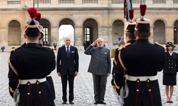 Prime Minister Narendra Modi accompanied by French Foreign Minister Laurent Fabius,  salutes during a welcoming ceremony in the courtyard of the Hotel des Invalides in Paris, France.