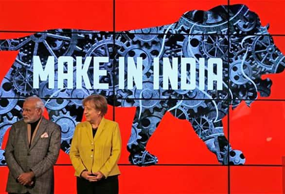 German Chancellor Angela Merkel and India's Prime Minister Narendra Modi, left, stand on the podium of the India booth during the opening of the industrial fair in Hanover, Germany, Monday, April 13, 2015.