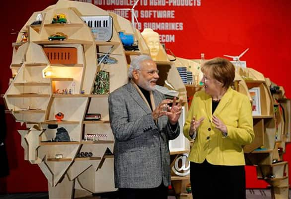German Chancellor Angela Merkel and India's Prime Minister Narendra Modi chat at the India booth during the opening of the industrial fair in Hanover, Germany, Monday, April 13, 2015.