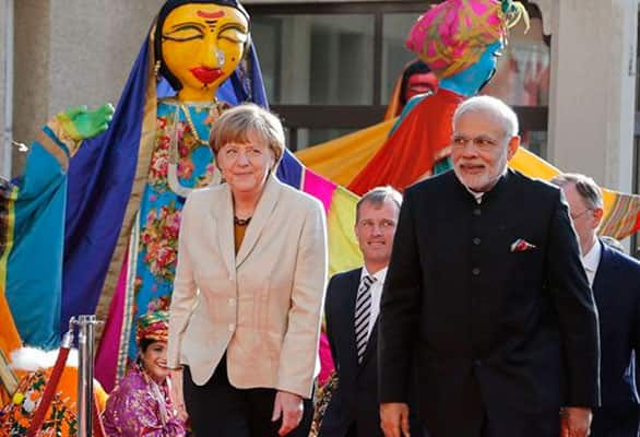 German Chancellor Angela Merkel, left, welcomes India's Prime Minister Narendra Modi, right, as a traditional Indian music group performs at the opening of the industrial fair in Hanover, Germany, Sunday, April 12, 2015.