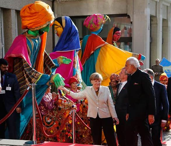German Chancellor Angela Merkel, center, welcomes India's Prime Minister Narendra Modi, right, as a traditional Indian music group performs at the opening of the industrial fair in Hanover, Germany, Sunday, April 12, 2015.