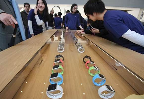Customers and staff look at models of Apple Watch displayed in a glass case at an Apple Store in Tokyo as Apple Watch made its debut Friday, April 10, 2015. Customers were invited to try them on in stores and order them online.