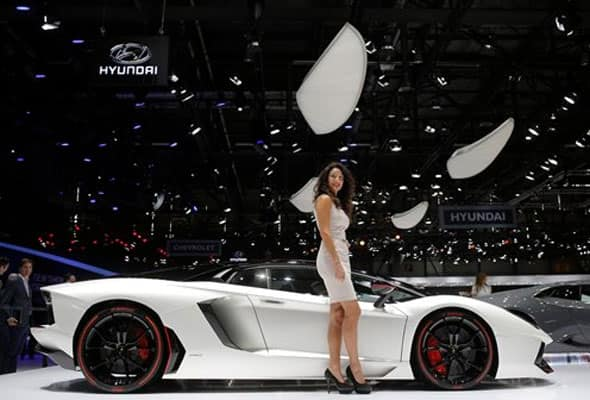A model poses in front of the new Lamborghini Aventador during the first press day of the Geneva International Motor Show Tuesday, March 3, 2015 in Geneva, Switzerland.