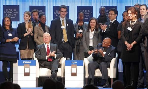 Klaus Schwab, founder of the World Economic Forum, left, and Archbishop Desmond Tutu, right, are surrounded by young global leaders during a session at the World Economic Forum in Davos.