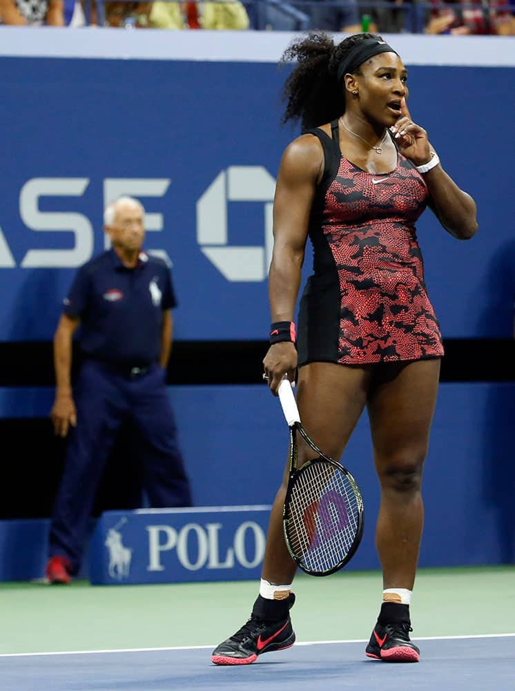Serena Williams motions for quiet during a quarterfinal match against Venus Williams at the U.S. Open tennis tournament.