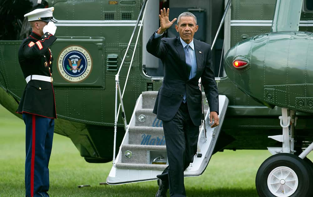 President Barack Obama waves upon arrival at the White House in Washington.