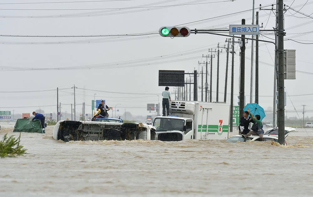 People wait for help as the vehicles are submerged in flooding in Joso, Ibaraki prefecture, northeast of Tokyo.