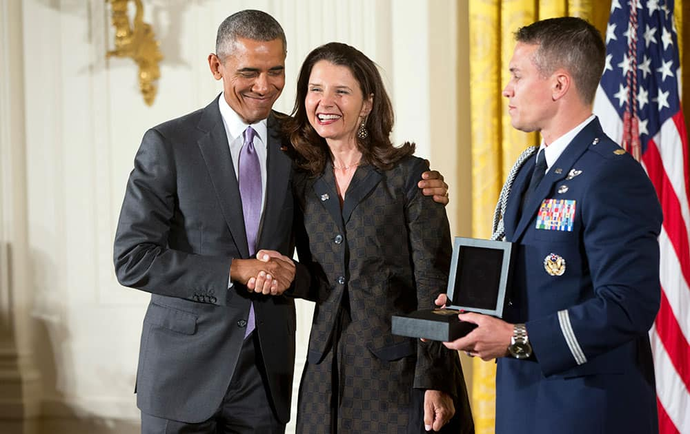 President Barack Obama awards the 2014 National Humanities Medal to Clemente Course In The Humanities of Annandale-On-Hudson, N.Y., and is received by Academic Director Marina van Zuylen during a ceremony in the East Room at the White House in Washington