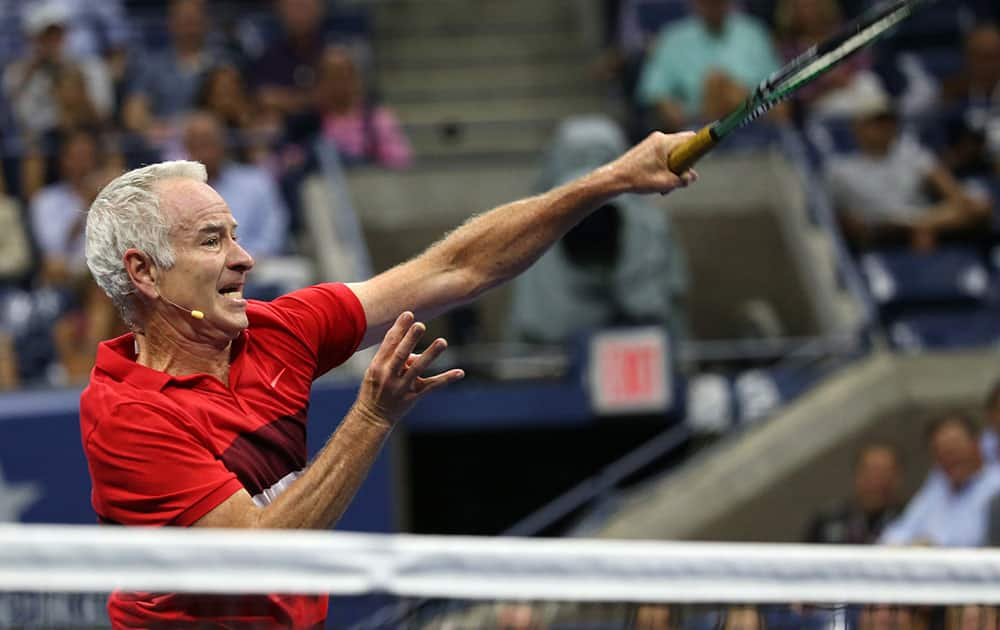 John McEnroe returns a shot as he and Michael Change play Jim Courier and Mardy Fish during an exhibition doubles match at the U.S. Open tennis tournament.