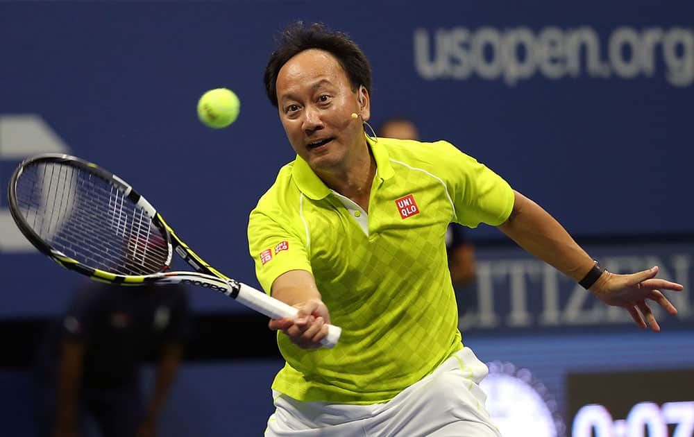 Michael Chang returns a shot to Jim Courier and Mardy Fish during an exhibition doubles match, with Chang teaming with John McEnroe, at the U.S. Open tennis tournament.