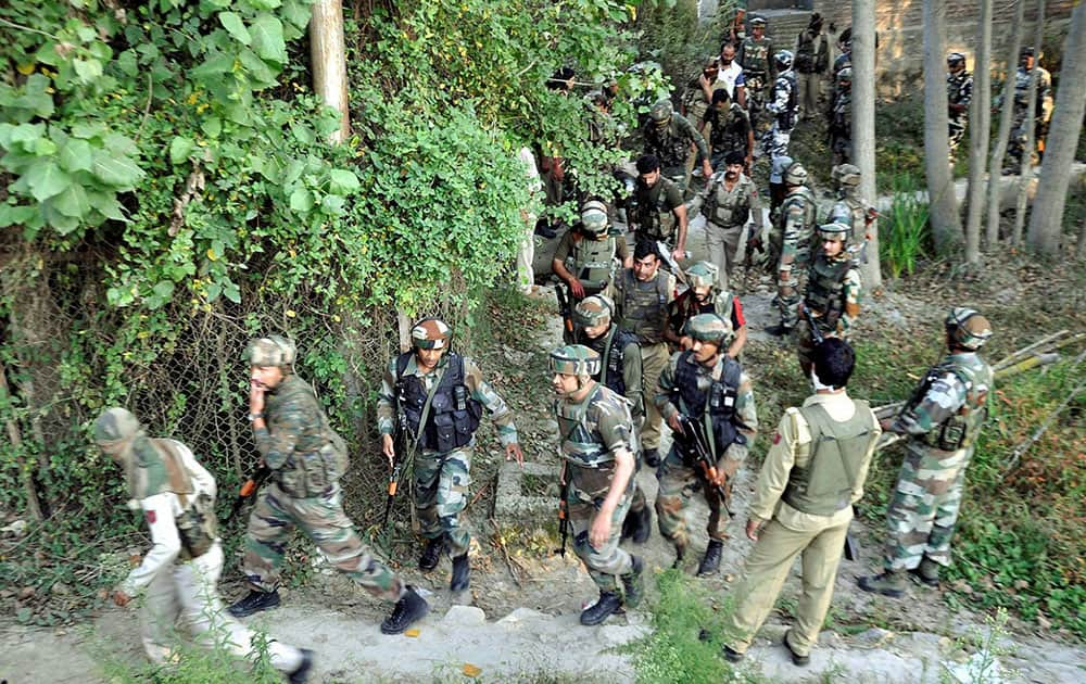 Army personnel rush towards the house where militant was hiding during an encounter,at Pulwama in Srinagar.